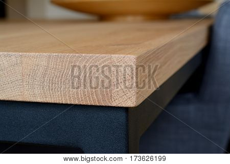 Corner of wooden table top made of oak wood closeup. Table top on black steel frame. Shallow depth of field.