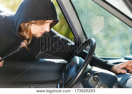 Anti theft system problem concept. Burglar thief man wearing black clothes breaking into car and stealing something