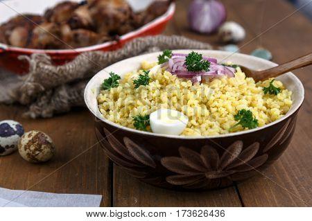 Eastern traditional wheat porridge - bulgur, in a clay bowl on dark wooden background