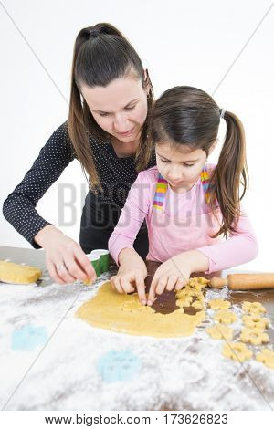 Mother and her daughter working in kitchen preparing pastry for cookies