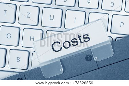 Costs - folder with text on computer keyboard