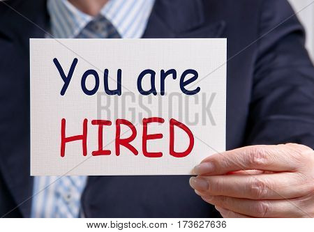 You are hired - Businesswoman with sign and text