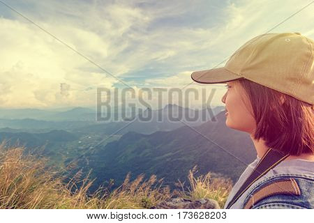 Vintage style hiker asian teen girl wear cap with happy looking beautiful landscape nature on top of high mountain at viewpoint Phu Chi Fa Forest Park Chiang Rai Thailand