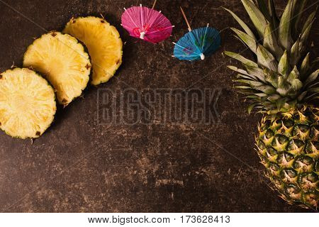 Ripe pineapple and cocktail umbrellas on a dark table with a marble texture with scratches. Cut fruit. Healthy eating. Going on a journey to the south. Journey concept