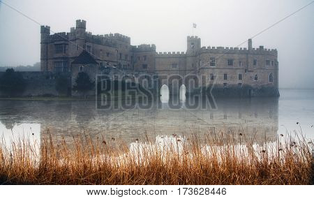 January 25, 2017 Leeds Castle, England: Panorama of the famous white stone castle and the grounds and its reflection on the water of the moat on a foggy day