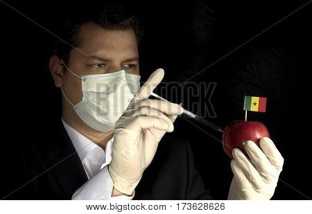 Young Businessman Injecting Chemicals Into An Apple With Senegalese Flag On Black Background