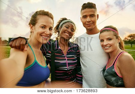 Smiley multicultural group of 4 people takes a group photo at sunrise in the park after their high intensity strenght training session