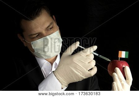 Young Businessman Injecting Chemicals Into An Apple With Ivory Coast Flag On Black Background