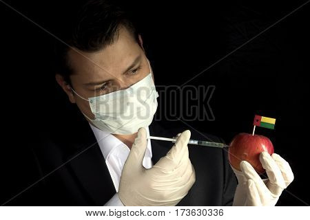 Young Businessman Injecting Chemicals Into An Apple With Guinea Bissau Flag On Black Background