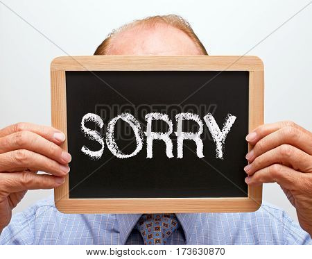 Sorry - Businessman holding blackboard with text