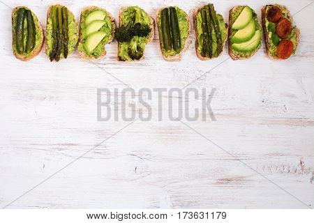 Green vegetarian sandwiches selection made with avocado courgette asparagus broccoli with one tomato sandwich top view