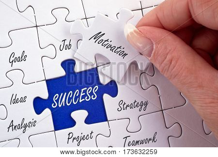 Success - Business concept puzzle with female hand and text