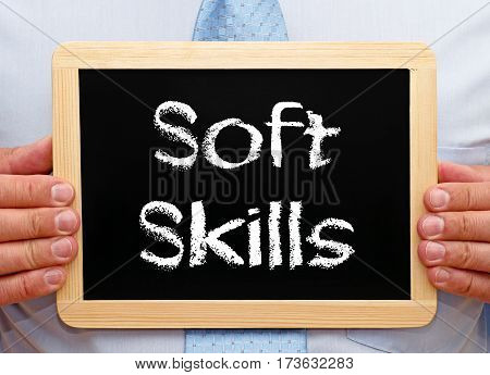Soft Skills - Businessman holding chalkboard with text