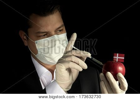 Young Businessman Injecting Chemicals Into An Apple With Danish Flag On Black Background