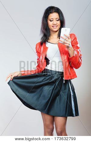 Technology and communication concept. Young attractive fashionable woman in red jacket using her mobile phone.
