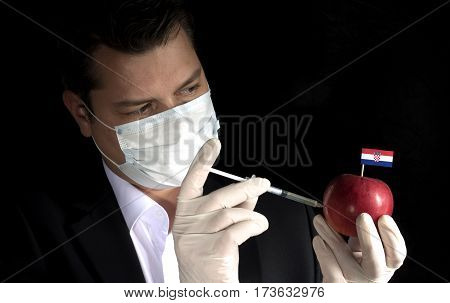Young Businessman Injecting Chemicals Into An Apple With Croatian Flag On Black Background