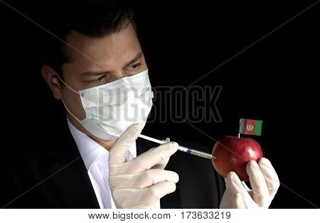 Young Businessman Injecting Chemicals Into An Apple With Afghan Flag On Black Background