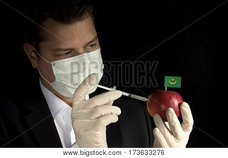 Young Businessman Injecting Chemicals Into An Apple With Mauritanian Flag On Black Background
