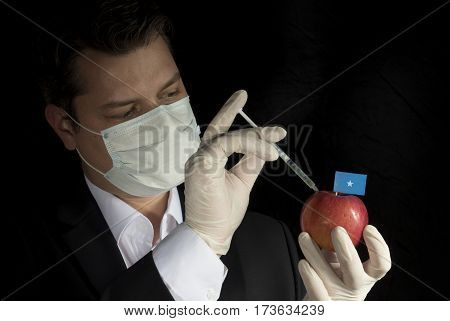 Young Businessman Injecting Chemicals Into An Apple With Somalian Flag On Black Background