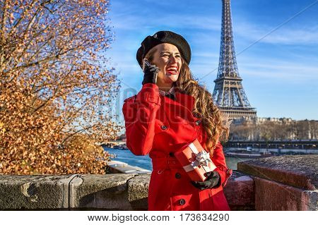 Woman In Paris Using A Mobile Phone And Holding Present Box