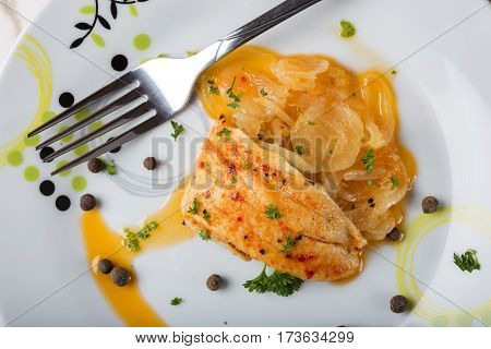 Marinated fish with onion sauce and herbs on plate