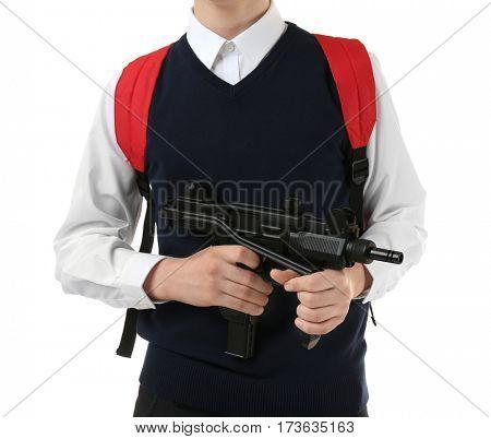 Schoolboy holding machine gun on white background