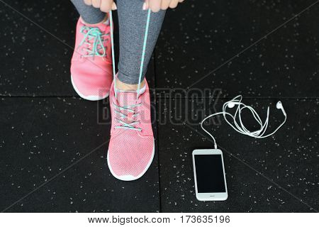 Young woman with mobile phone tying shoelaces in gym