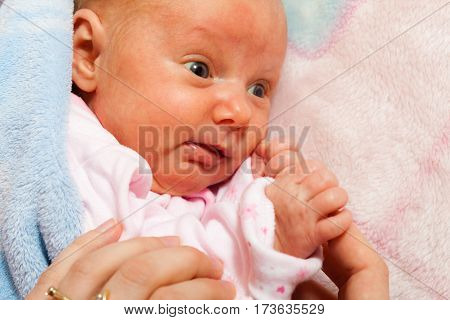 Childhood innocence concept. Little adorable newborn baby lying on bed with many blankets.