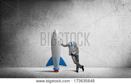 Headless businessman in empty room leaning on rocket
