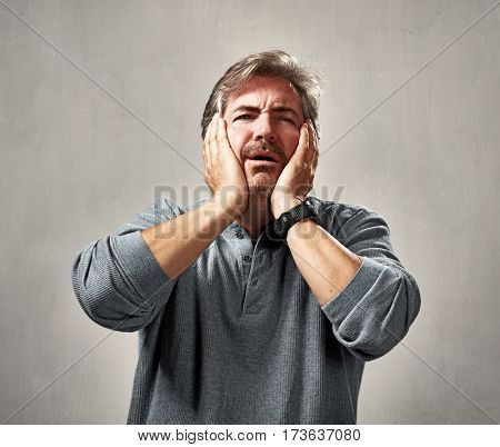 Despaired unhappy man portrait over gray wall background