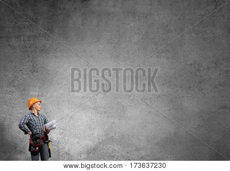 Engineer woman with blueprint against concrete wall background