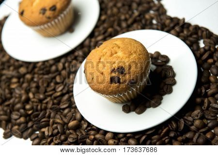 Delicious muffin with chocolate surrounded by beautiful Arabica coffee beans.