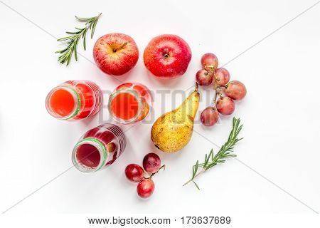 colorful plastic bottles with fruit drinks on white table background top view