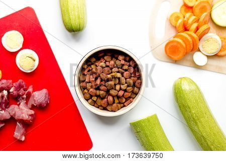 Set of animal dry food with raw meat, fresh vegetables and cut eggs on white kitchen table background top view