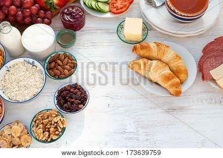 Top view of the healthy continental breakfast ham cheese cereals toast nuts jam vegetables croissants selective focus copy space for text