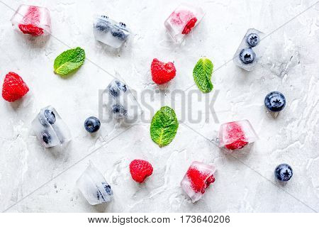 Frozen bueberrie and raspberrie in ice cubes with mint on stone table background top view