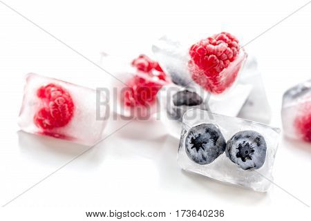 frozen fresh blueberry and raspberry in ice cube on white table background