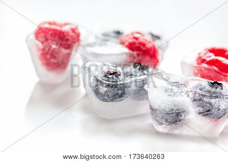Ice cubes with frozen fresh berries on white table background