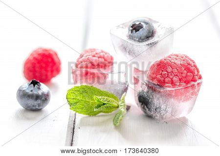 fresh blueberries and raspberries with mint leaf in ice cubes on white wooden background