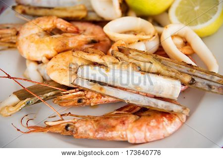 Seafood grill on a small platter : langoustines ,  calamari , shrimps