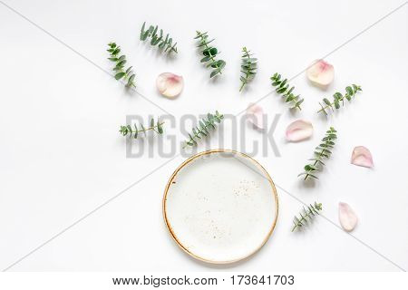mock up in pastel colors with rose petals and eucalyptus on white table background top view