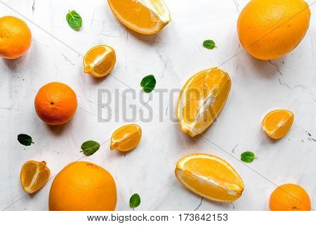 Fresh orange fruits with mint leaves on kitchen table background top view pattern