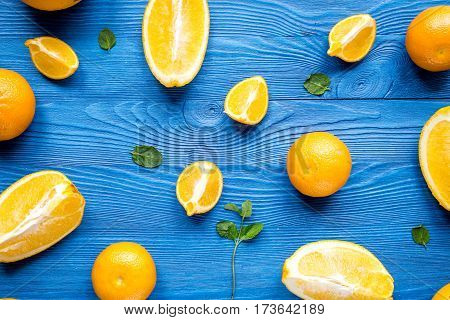 Cut fresh oranges for juicy breakfast with mint on blue background top view pattern