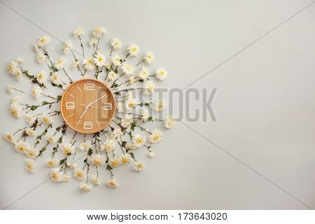 Clock decorated with flowers on light wall