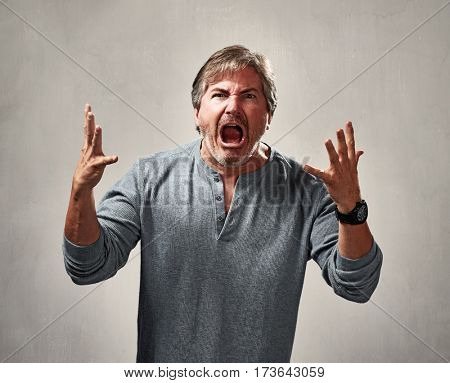 Aggressive mad man portrait over gray background