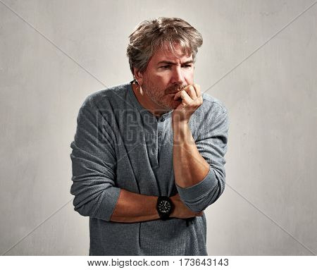 insecure worried mature man portrait over gray background