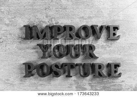 Black letters forming phrase IMPROVE YOUR POSTURE on gray background