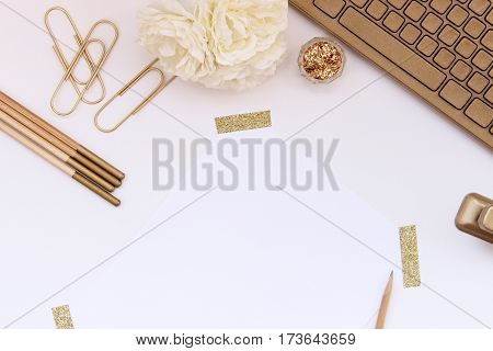 Chic and elegant white and gold desktop with gold office supplies, keyboard, flowers and blank paper for copy.