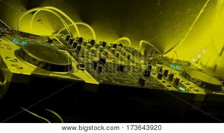 disc jockey mixer with yellow tones night club