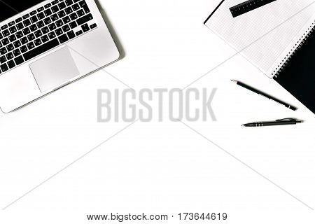 White office desk frame with paper blank and supplies. Laptop, notebook, pen, clips, glasses and office supplies on white background. Flat lay, top view, mockup.
